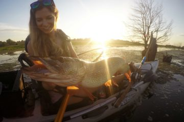 Girl fishing from kayak for pike.