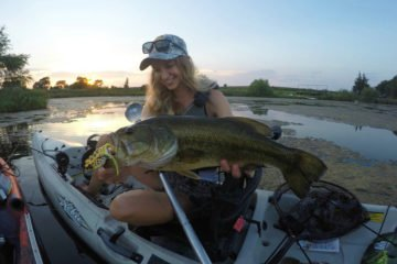 Top tips for catching bass & other fish. Female angler holds topwater bass in a Hobie Revolution 13.